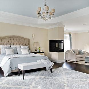 Diseño de dormitorio principal, clásico renovado, extra grande, con paredes beige, suelo de madera oscura, chimenea de doble cara y marco de chimenea de metal