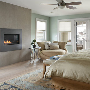 Large transitional master bedroom photo in Other with blue walls, a concrete fireplace and a standard fireplace