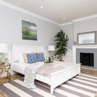 Ejemplo de habitación de invitados tradicional renovada, grande, con paredes grises, suelo de madera clara, chimenea tradicional y marco de chimenea de ladrillo