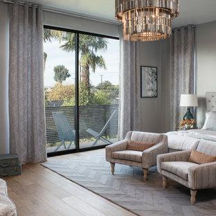 Ispirazione per una camera matrimoniale classica con pareti grigie, pavimento in legno massello medio e camino ad angolo