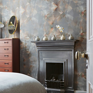 Photo of a classic bedroom in London with grey walls and a standard fireplace.