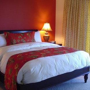 Esempio di una camera degli ospiti tropicale con pareti rosse e moquette