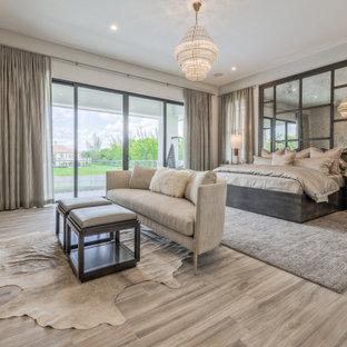 Ejemplo de dormitorio principal, tradicional renovado, grande, sin chimenea, con paredes beige, suelo de baldosas de porcelana y suelo beige