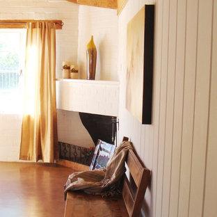 Пример оригинального дизайна: хозяйская спальня среднего размера в стиле современная классика с белыми стенами, бетонным полом, угловым камином и фасадом камина из кирпича