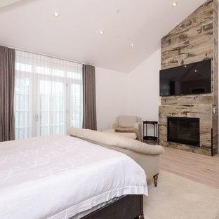 Modelo de dormitorio principal, tradicional renovado, grande, con paredes blancas, suelo de madera clara, chimenea tradicional, marco de chimenea de madera y suelo beige