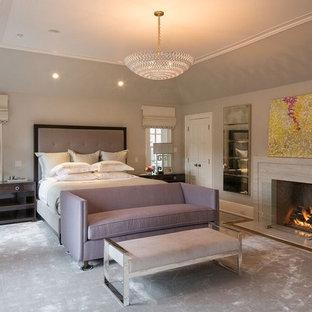 Стильный дизайн: большая хозяйская спальня в стиле современная классика с серыми стенами, ковровым покрытием, стандартным камином, фасадом камина из камня и серым полом - последний тренд