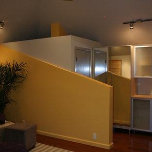 サンフランシスコの中サイズのコンテンポラリースタイルのおしゃれな客用寝室 (黄色い壁、無垢フローリング、茶色い床) のインテリア