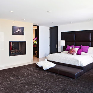 Bedroom - huge contemporary master light wood floor bedroom idea in Los Angeles with white walls, a stone fireplace and a two-sided fireplace