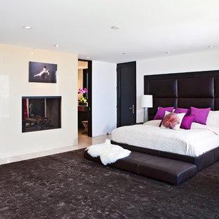 На фото: огромная хозяйская спальня в современном стиле с белыми стенами, светлым паркетным полом, фасадом камина из камня и двусторонним камином с