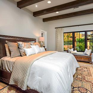 Example of a tuscan master medium tone wood floor bedroom design in Phoenix with gray walls