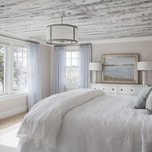 Example of a large beach style master light wood floor and beige floor bedroom design in Boston with beige walls and no fireplace