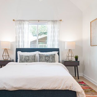 Example of a mid-sized transitional master light wood floor and beige floor bedroom design in Austin with white walls