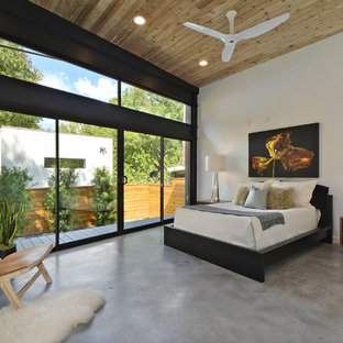 Trendy master concrete floor and gray floor bedroom photo in Austin with white walls