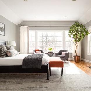 Пример оригинального дизайна: большая хозяйская спальня в стиле современная классика с серыми стенами, паркетным полом среднего тона, стандартным камином, фасадом камина из камня и коричневым полом