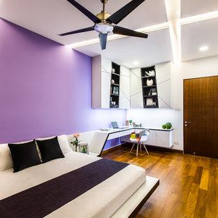 Imagen de dormitorio minimalista, de tamaño medio, con paredes púrpuras y suelo de madera en tonos medios
