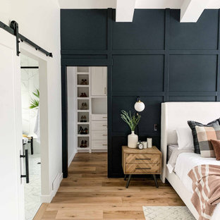 Imagen de dormitorio principal, clásico renovado, grande, sin chimenea, con paredes negras, suelo de madera en tonos medios y suelo marrón