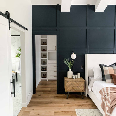 Inspiration for a large transitional master medium tone wood floor and brown floor bedroom remodel in Other with black walls and no fireplace