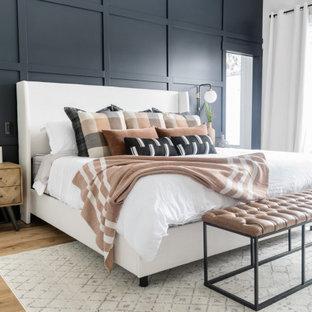 Modelo de dormitorio principal, clásico renovado, grande, sin chimenea, con paredes negras, suelo de madera en tonos medios y suelo marrón