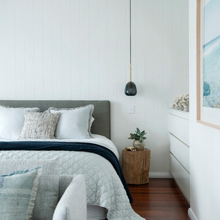 Mid-sized beach style master bedroom in Perth with white walls, dark hardwood floors and brown floor.