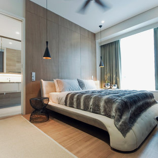 This is an example of a contemporary bedroom in Singapore with light hardwood flooring.
