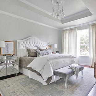 Idées déco pour une grande chambre parentale classique avec un sol en bois brun et un mur gris.