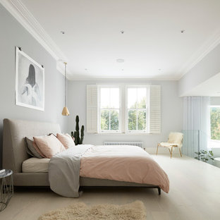 Design ideas for a large contemporary master bedroom in London with grey walls and light hardwood flooring.