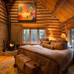 Diseño de dormitorio principal, rústico, grande, con suelo de madera clara, estufa de leña y marco de chimenea de ladrillo
