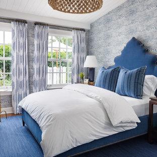Bedroom - tropical guest medium tone wood floor and brown floor bedroom idea in Miami with blue walls