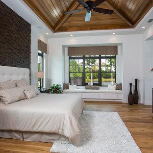 Ispirazione per una camera matrimoniale tropicale con pareti bianche e pavimento in legno massello medio