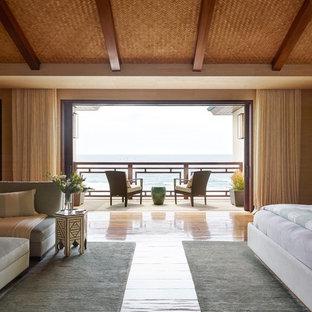 Foto de dormitorio principal, tropical, con suelo de madera en tonos medios