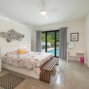 Imagen de dormitorio principal, minimalista, de tamaño medio, con paredes blancas y suelo de cemento