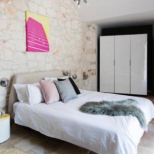 Immagine di una camera matrimoniale mediterranea con pavimento in pietra calcarea e pareti beige