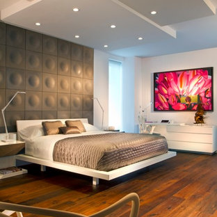 Источник вдохновения для домашнего уюта: спальня в современном стиле с белыми стенами, паркетным полом среднего тона, оранжевым полом и акцентной стеной