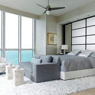 Large modern master bedroom in Miami with beige walls, marble floors and no fireplace.