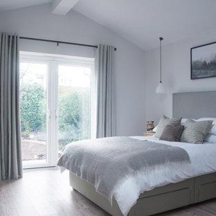 Foto di una camera degli ospiti classica di medie dimensioni con pareti grigie, pavimento in laminato e pavimento marrone