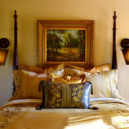 Masters Residence - Bronze and gold silk wall sconces flank a cherry poster bed with gold, copper and olive green embroidered shams and duvet cover. This warm, traditional but luxe guest room is dressed up by metallic gold touches.