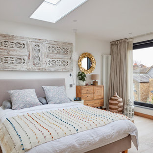 Design ideas for a contemporary guest bedroom in London with white walls and light hardwood flooring.