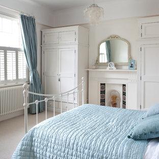 Esempio di una camera matrimoniale classica con pareti beige, moquette e camino classico