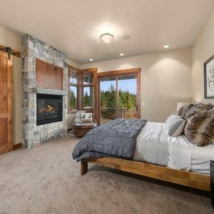 Foto de dormitorio principal, rústico, con paredes blancas, moqueta, chimenea lineal, marco de chimenea de piedra y suelo beige