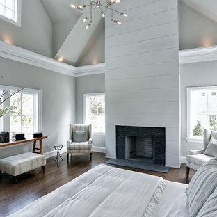 ニューヨークの中サイズのトランジショナルスタイルのおしゃれな主寝室 (グレーの壁、濃色無垢フローリング、標準型暖炉、木材の暖炉まわり、茶色い床) のレイアウト