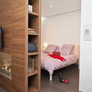 Пример оригинального дизайна: спальня среднего размера в современном стиле с белыми стенами, полом из керамогранита, коричневым полом, двусторонним камином и фасадом камина из дерева
