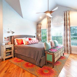 Bild på ett eklektiskt sovrum, med grå väggar, mellanmörkt trägolv och orange golv