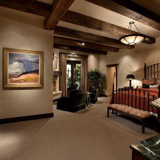 Rustik inredning av ett stort huvudsovrum, med beige väggar, heltäckningsmatta, en öppen hörnspis och en spiselkrans i gips