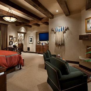 Неиссякаемый источник вдохновения для домашнего уюта: большая хозяйская спальня в стиле рустика с бежевыми стенами, ковровым покрытием, угловым камином и фасадом камина из штукатурки