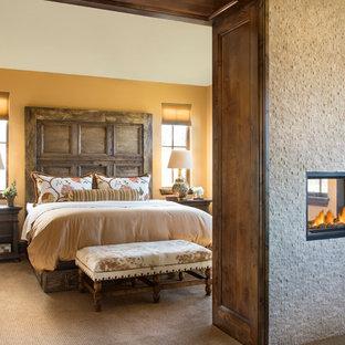 Идея дизайна: большая хозяйская спальня в средиземноморском стиле с ковровым покрытием, фасадом камина из плитки и двусторонним камином