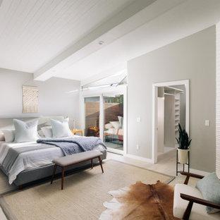 Bild på ett retro sovrum, med grå väggar, ljust trägolv, en öppen hörnspis, en spiselkrans i trä och beiget golv
