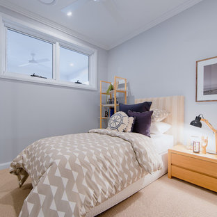 This is an example of a beach style guest bedroom in Gold Coast - Tweed with blue walls, carpet and beige floor.