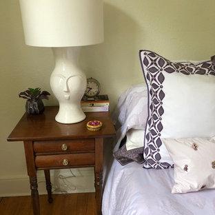Foto de dormitorio principal, clásico renovado, de tamaño medio, con paredes amarillas, suelo de madera en tonos medios, chimenea de esquina, marco de chimenea de ladrillo y suelo marrón