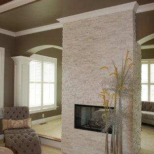 Ejemplo de dormitorio principal, tradicional, de tamaño medio, con paredes beige, moqueta, chimenea de doble cara y marco de chimenea de piedra