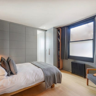 Design ideas for a small eclectic guest bedroom in London with grey walls, light hardwood flooring and brown floors.